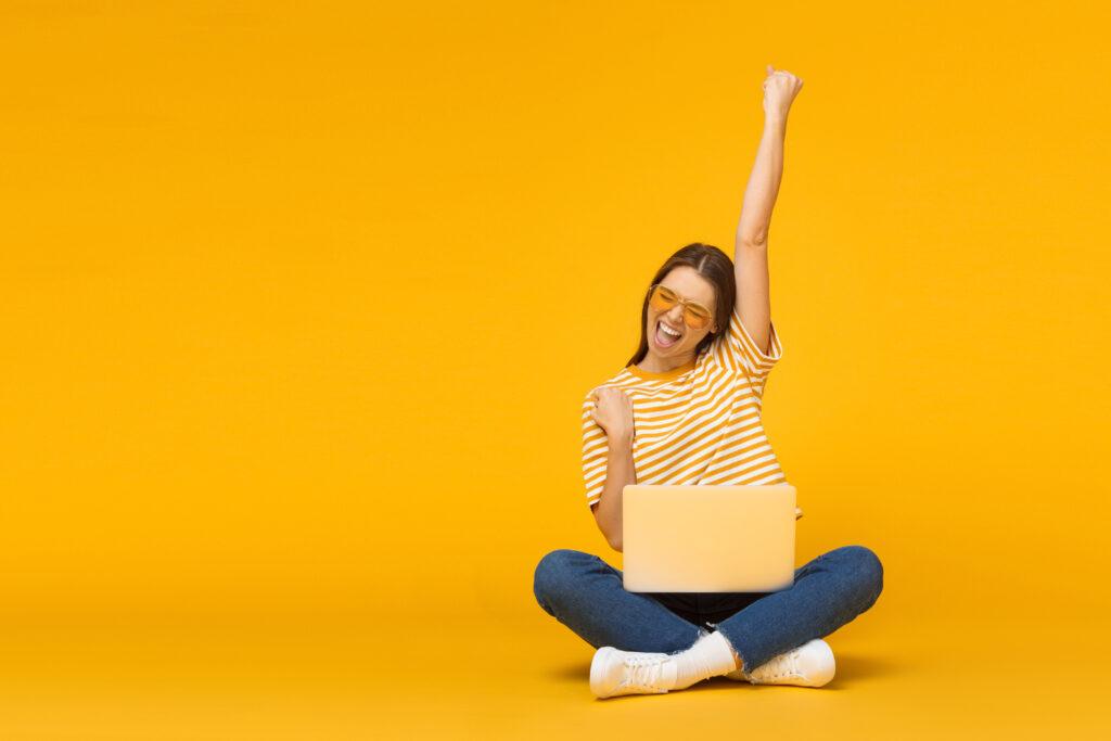 Jeune femme heureuse assise par terre avec un ordinateur
